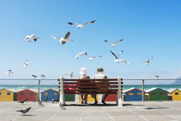 couple assis sur un banc face aux cabanons colorés de muizenberg