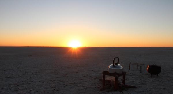 petit feu de camp dans le désert du botswana au coucher de soleil
