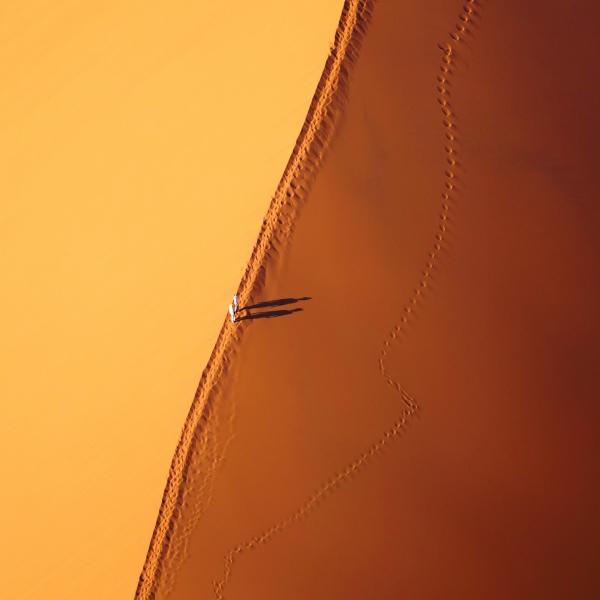 deux voyageurs marchent sur la crête d'une dune du désert du namib
