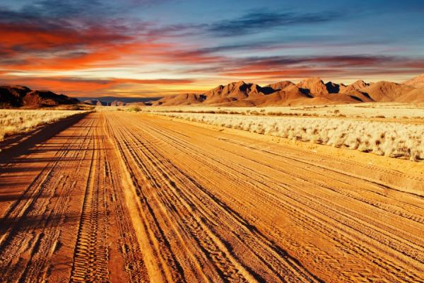 piste sablonneuse et désertique de la route D707 au coucher du soleil