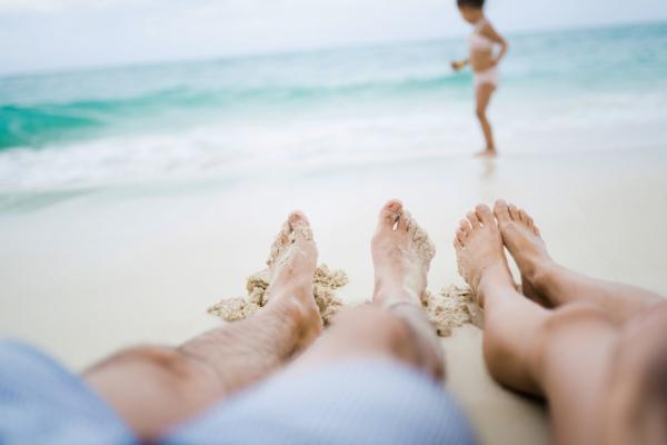 Zoom sur les jambes d'un couple avec leur fille et la mer en fond