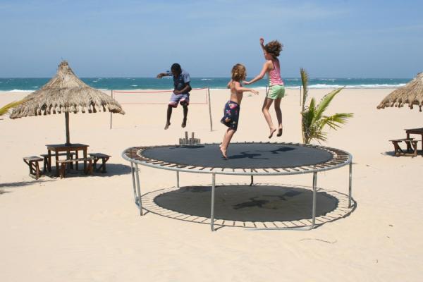 Trois enfants s'amusent sur un trampoline sur la plage