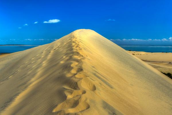 Grande dune de Bazaruto avec des empreintes de pas sous un ciel bleu