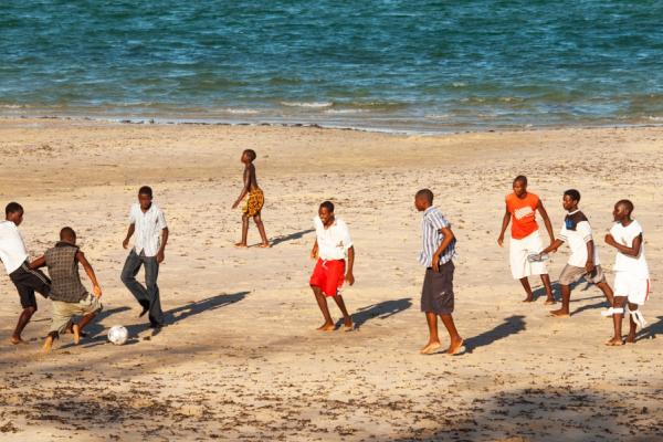 Un groupe d'hommes joue au foot sur la plage
