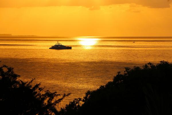 Un bateau navigue sur l'océan au coucher du soleil totalement orangé