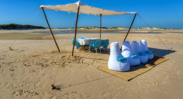 Une table dressée et des sièges blancs et bleus sur une plage déserte