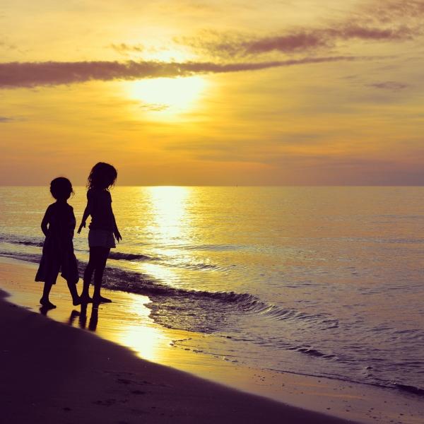Deux enfants sur la plage ont les pieds dans l'eau au coucher de soleil