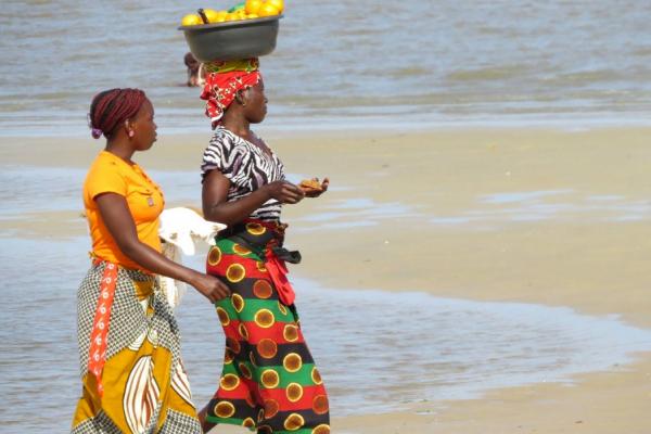 2 femmes marchent sur la plage de Vilanculos, l'une porte un panier