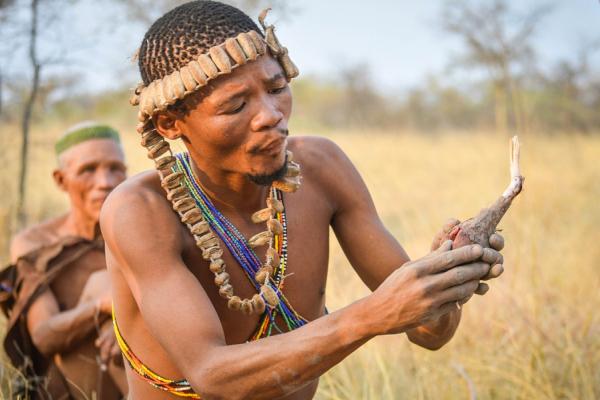 homme san en habit traditionnel sur fond de savanne