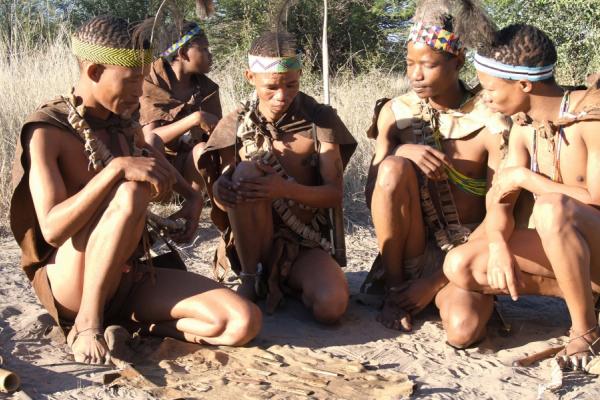 Accroupis sur le sable du kalahari, un groupe de San joue