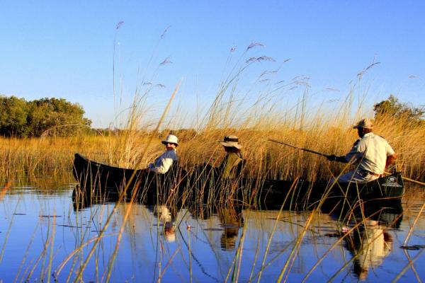 Un guide local conduit deux touristes en mokoro, barque traditionnelle