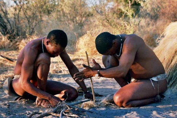 Deux hommes San accroupis en train de faire du feu avec un bâton