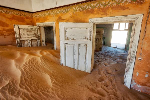 L'intérieur d'une maison et ses portes dont le sable regorge