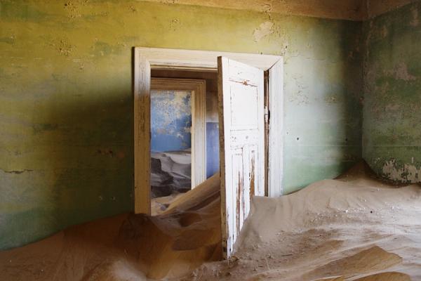 L'intérieur d'une maison abandonnée et envahie par le sable