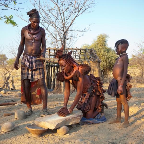 Une femme San travaille accroupis. Son enfant et son mari la regardent