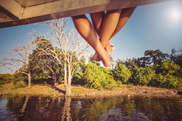 Deux paires de jambes entremelées dépassent d'un toit d'un bateau