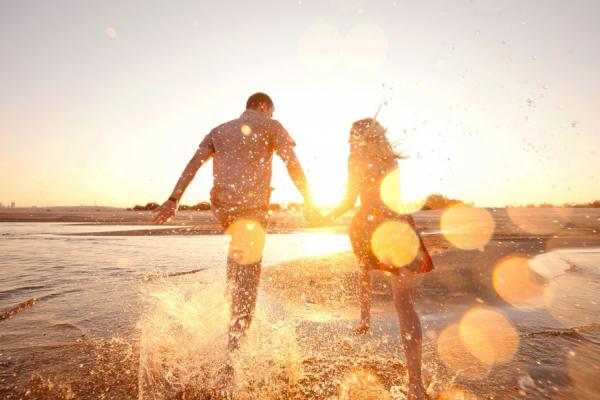 De dos, deux amoureux courent vers l'eau en se tenant la main