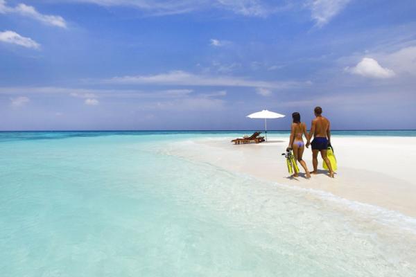 2 transats attendent ce couple qui longe la mer en portant leur palmes