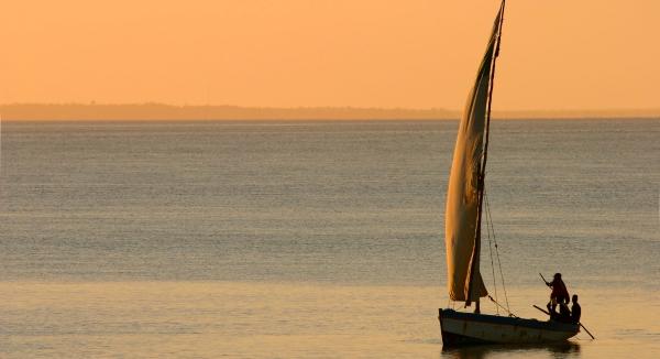 Au crépuscule, sous un ciel orangé, un boutre navigue sur l'océan