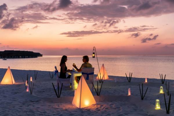 Au coucher de soleil, un couple partage un dîner romantique sur la plage