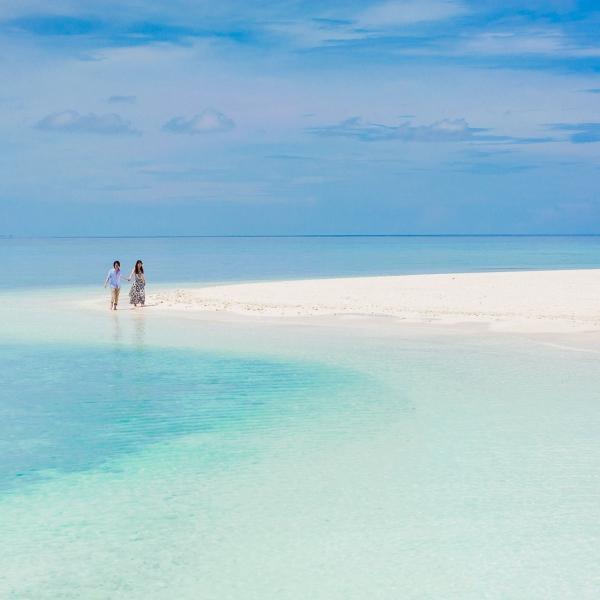Un couple se balade dans un décor idylle d'une ile déserte