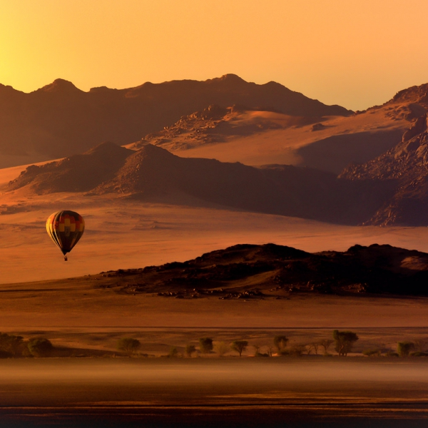 une montgolfière au dessus de la région du Namib au coucher du soleil