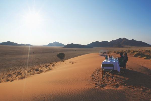 Seul au cœur des dunes du Namib, un couple déjeune en admirant la vue