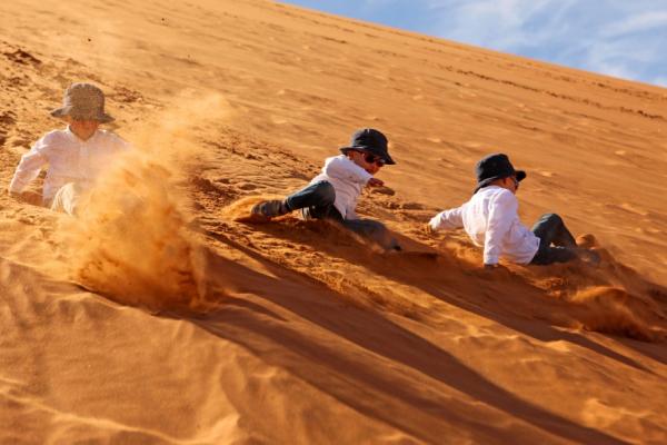 3 enfants s'amusent en dévalant les pentes des dunes ocres du Namib