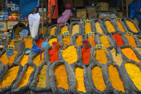 Des sacs d'épices colorées aux tons orangés sur le stand d'un marché