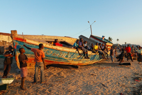 Des habitants et enfants évoluent autour d'un bateau sur la plage