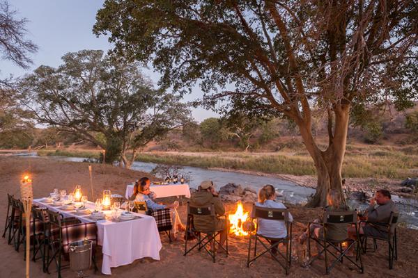 Campement en brousse avec table dressée et chaises au coin du feu