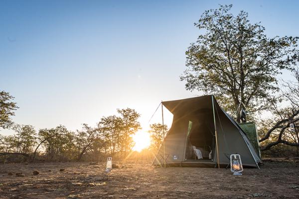 Une tente dôme dans la brousse avec ses lanternes et sa douche privée