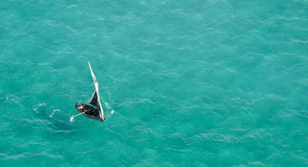 Vue du ciel, un boutre évolue dans l'océan turquoise du Mozambique