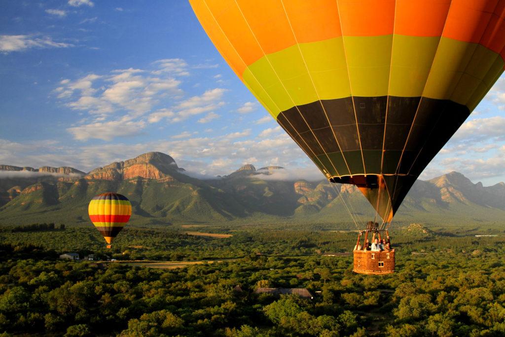 Deux montgolfières survolent un magnifique paysage montagneux et vert