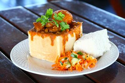 Pain farci de plat mijoté garni d'herbes de de riz sur une assiette blanche