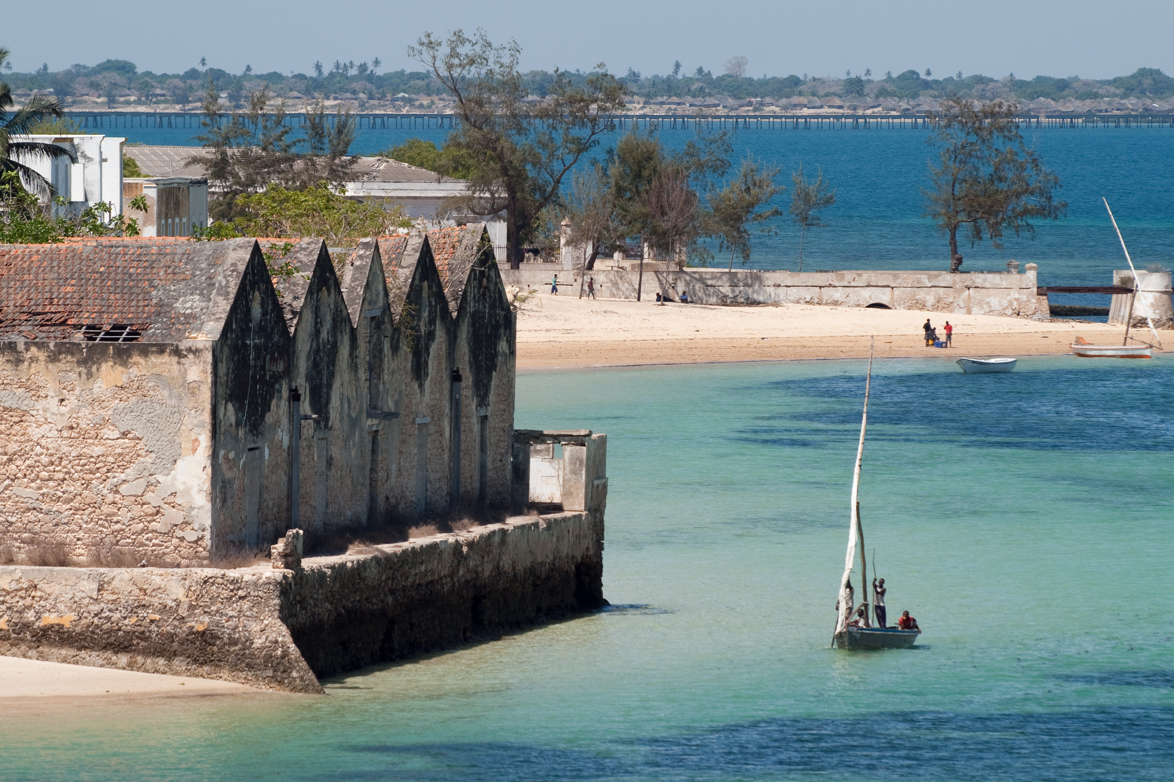 un boutre sur l'eau turquoise approche du rivage de l'île de mozambique