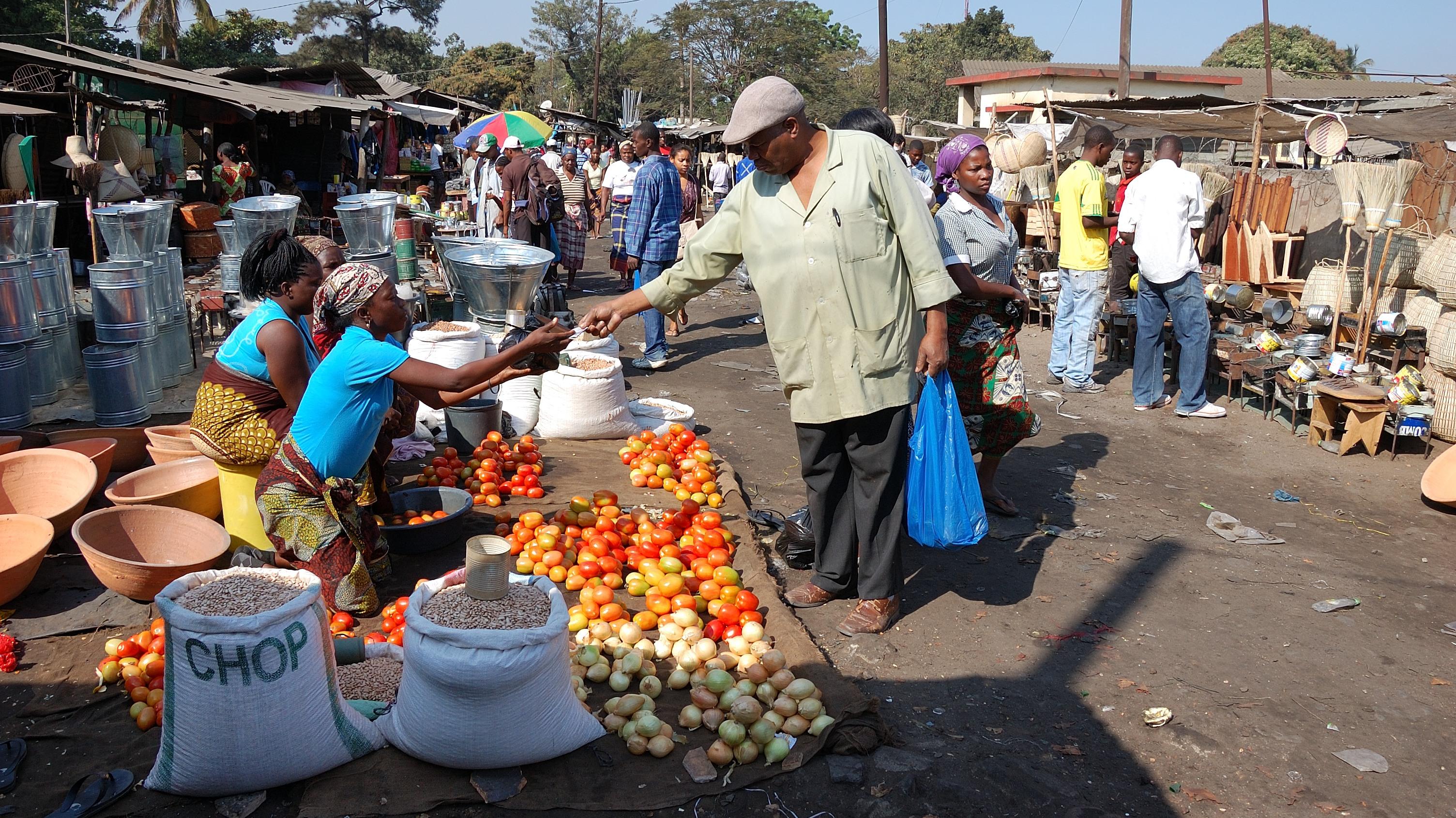 un homme achète des fruits et légumes dans les rues du marché à Maputo
