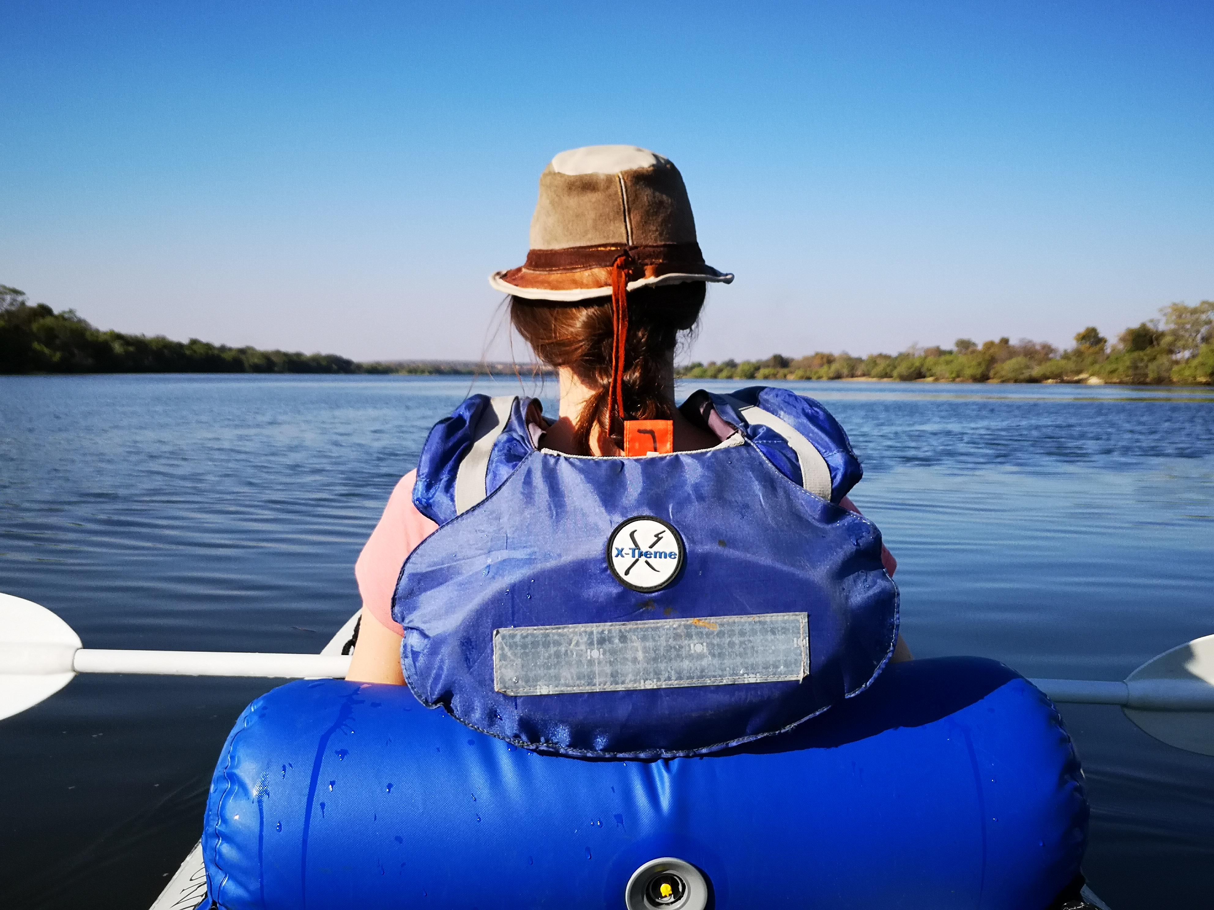 Une personne vue de dos se balade en kayak dans la reserve de zambezi au botswana