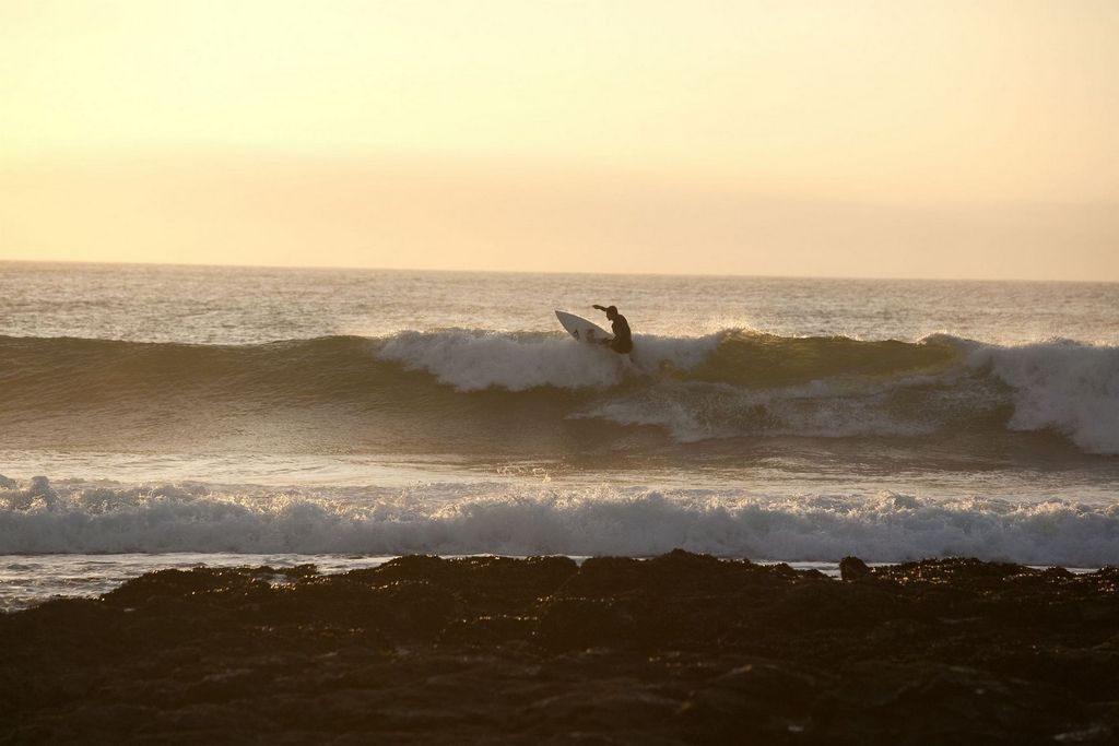 Surfeur maitrisant la vague de Jeffrey's Bay sous le soleil couchant d'Afrique du Sud