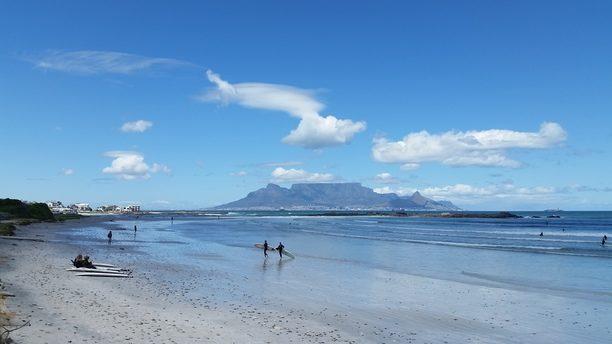 quelques surfeurs sur la plage de big bay avec Table Mountain en fond