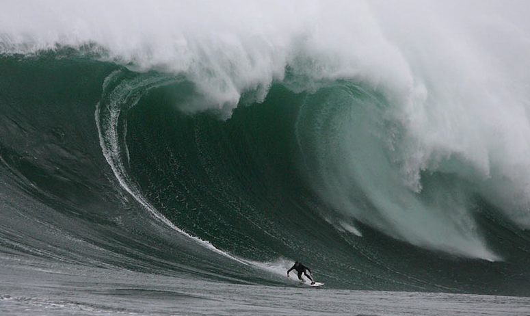 un surfeur professionnel glisse sur les vagues immenses de dungeons