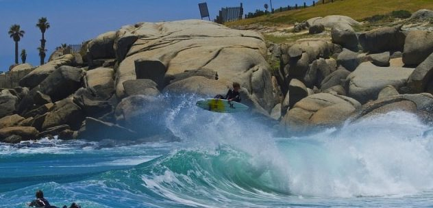 un surfeur en plein saut au dessus d'une vague avec des rochers derrière