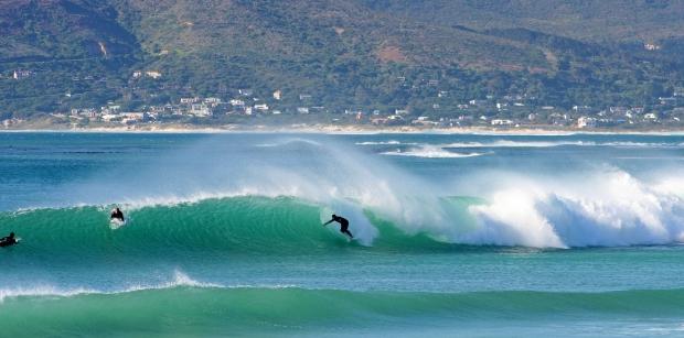 trois surfeurs surfent une vague avec derrière les montagnes de Kommetjie