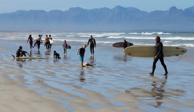 Sur la plage, petits et grands avec leur planche s'apprêtent à aller surfer