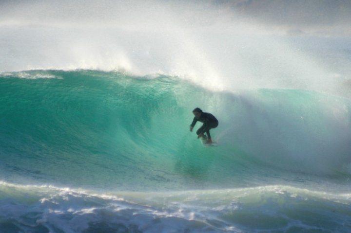 un surfeur à l'intérieur d'une vague aux tonalités turquoise