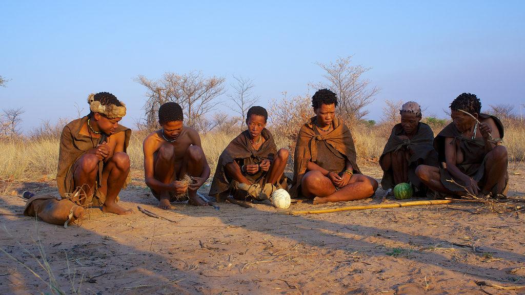 Six membres de la tribu des san se repose, assis sur le sol terreux du Central Kalahari