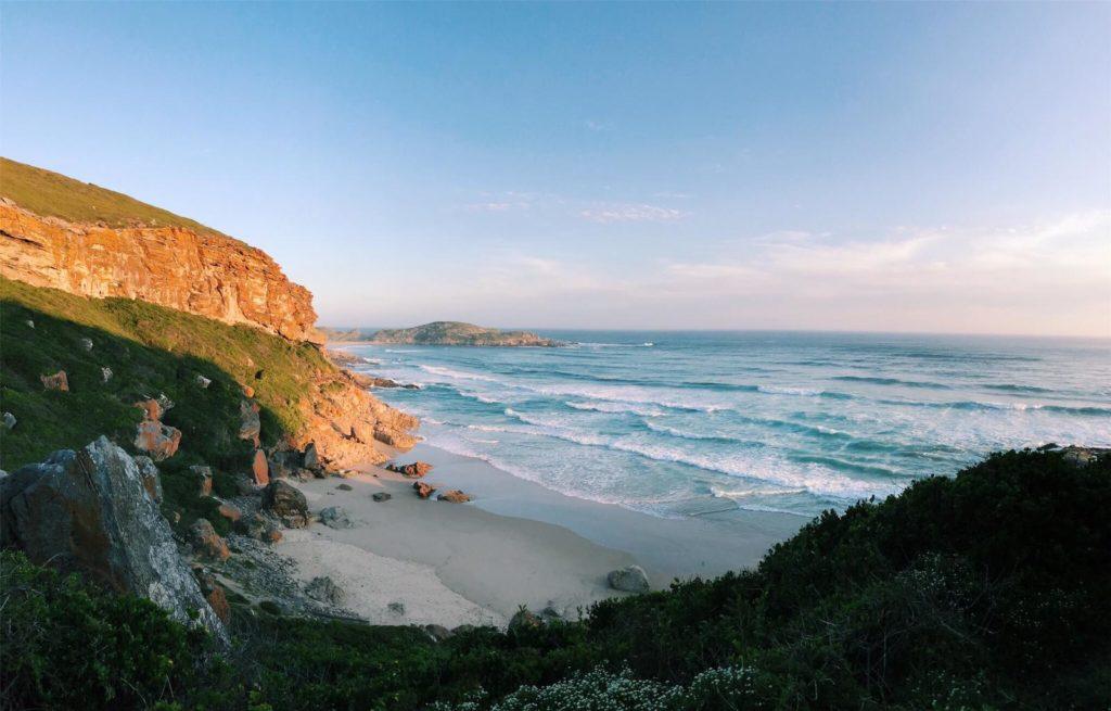Paysage donnant sur la plage de Robberg ainsi que sur les rochers orangés de la promenade