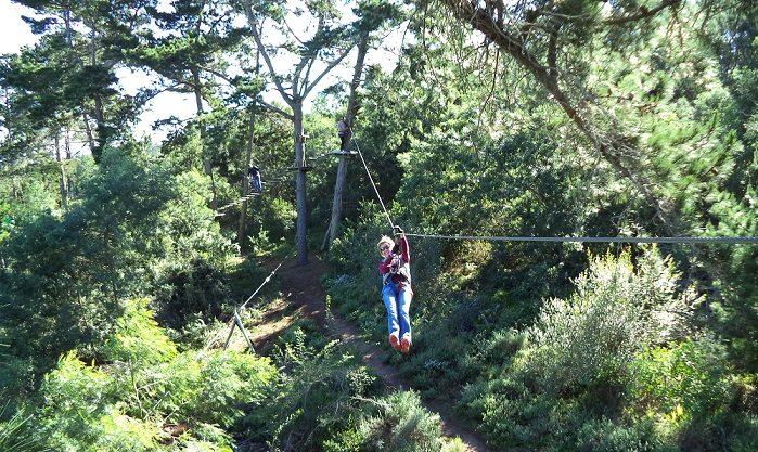 Joyeuse une femme descend sur la tyrolienne lors d une session d accrobranche