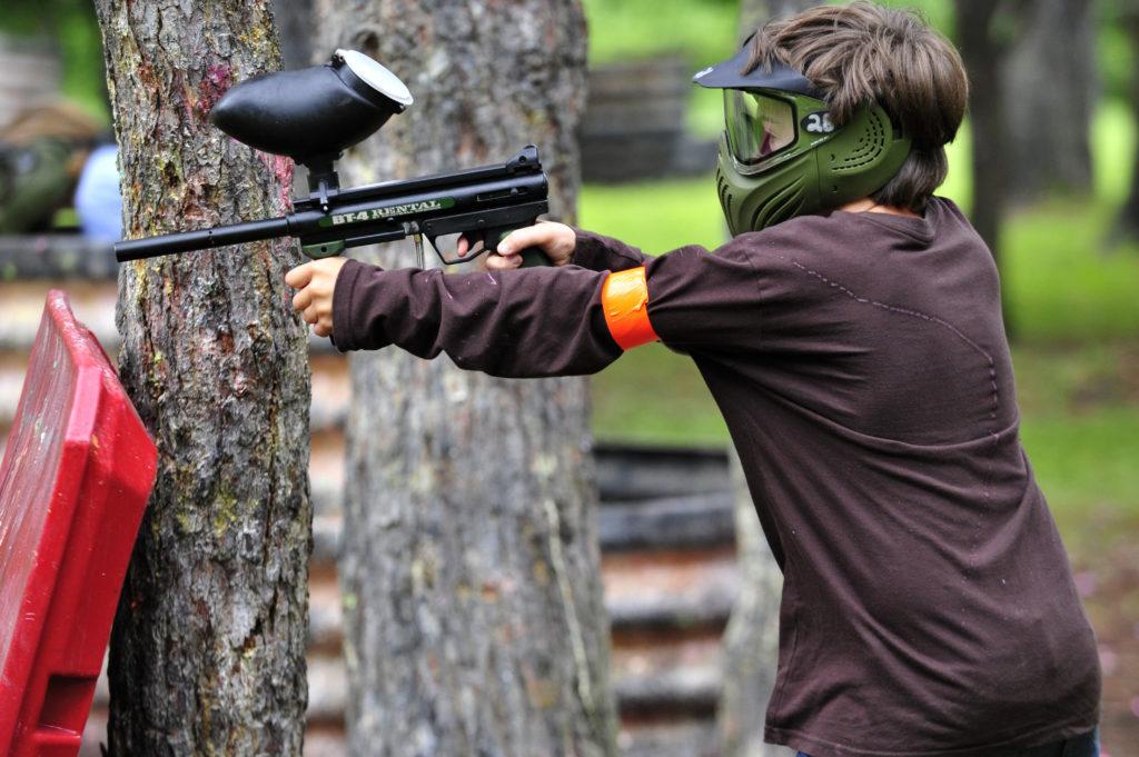 Pret a tirer un jeune garcon vise son adversaire lors d une session de paintball
