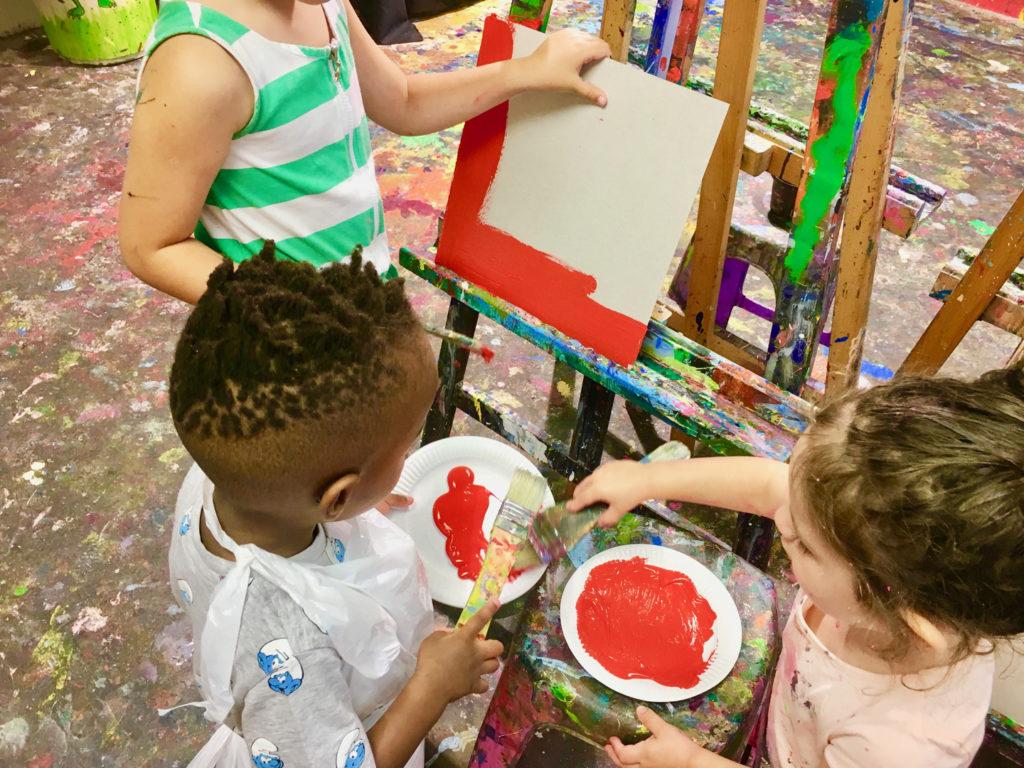 Trois enfants se préparent à appliquer de la peinture sur une toile vierge